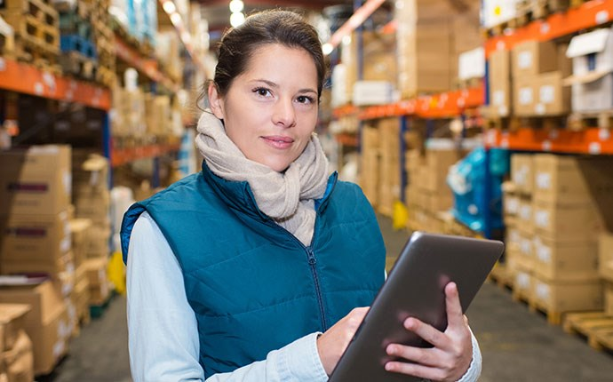 Woman in distribution center holding a tablet with eTurns on it to reduce forecast error.